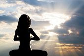 A silhouette of a woman sitting in yoga position, meditating against sunset sky. Zen, meditation poster