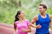 Healthy lifestyle - Running fitness couple jogging laughing, talking outside on road in beautiful nature. Multiracial sports couple, Asian woman model and man fitness model exercising smiling happy. poster