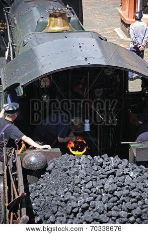Stoking the boiler on steam locomotive.