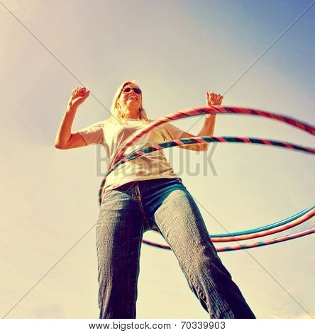 a woman hula hooping on a clear day toned with a retro vintage instagram filter