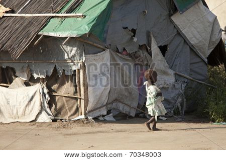 BOR, SOUTH SUDAN-DECEMBER 3 2010:Unidentified malnourished child walks past the shack she and her family live in in South Sudan