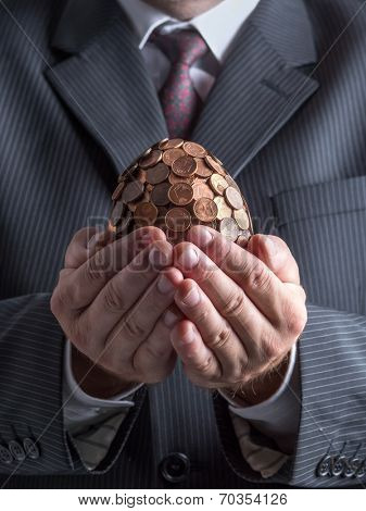 Businessman wearing suit holding one eurocent egg in his hands