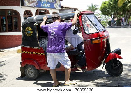 Tourist talks about a journey with the driver of tuk-tuk