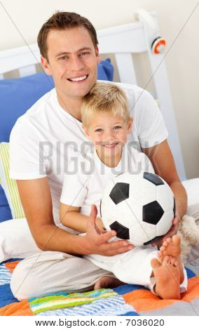 Close-up Of A Little Boy And His Father Playing With A Soccer Ball