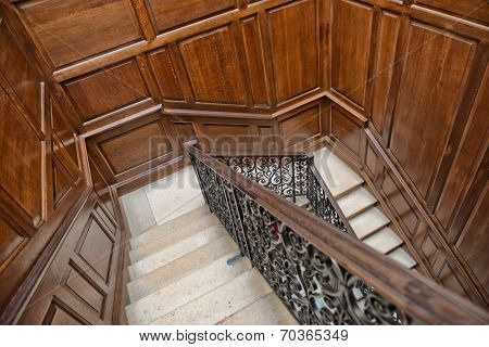Winding interior staircase with wood paneling on the walls and an ornate wrought iron and oak bannister viewed looking down the treads from above