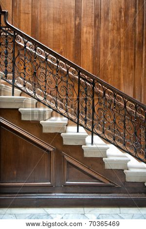 Flight of old ornate interior stairs with a decorative wrought iron bannister and wood paneling on the walls, view from the side