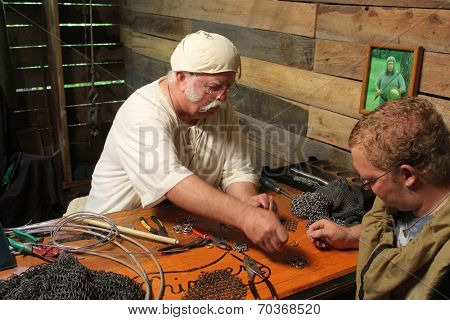 MUSKOGEE, OK - MAY 24: A crafter makes leather and metal armor belt at the Oklahoma 19th annual Renaissance Festival on May 24, 2014 at the Castle of Muskogee in Muskogee, OK