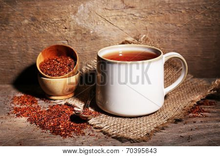 Cup of tasty rooibos tea, on wooden table poster