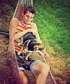 a young man in a hammock cuddling with his chihuahua beagle mix dog toned with a retro vintage instagram filter poster