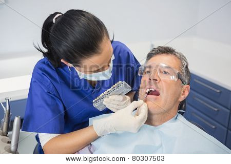 Dentist comparing teeth whitening of her patient in dental clinic poster