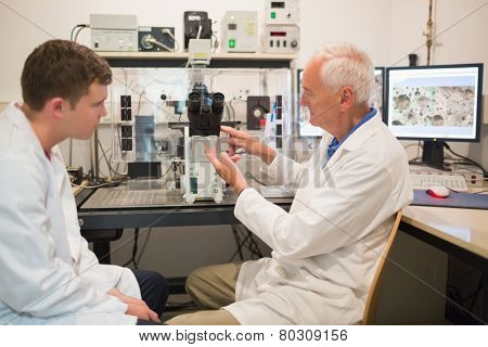 Biochemist using large microscope and computer with student at the university