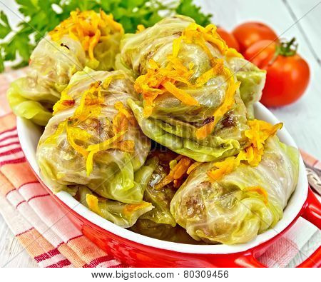 Stuffed cabbage meat in cabbage leaves with roasted carrots in a roasting pan on a red napkin, tomatoes with parsley on a light background boards poster