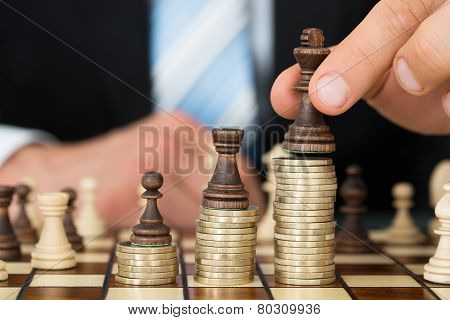 Businessman Placing Chess Pieces On Stacked Coins