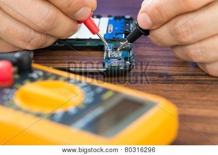 Human Hand  Repairing Cellphone With Multimeter