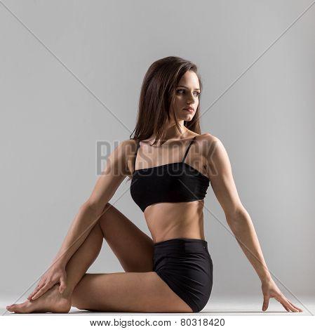 Beautiful sporty yogi girl practices yoga asana doing Ardha Matsyendrasana Half Lord of the Fishes Pose Half Spinal Twist Pose Vakrasana on grey background low key shot poster