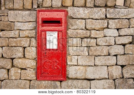 traditional old fashioned English red postbox mounted in a cotswold stone wall poster