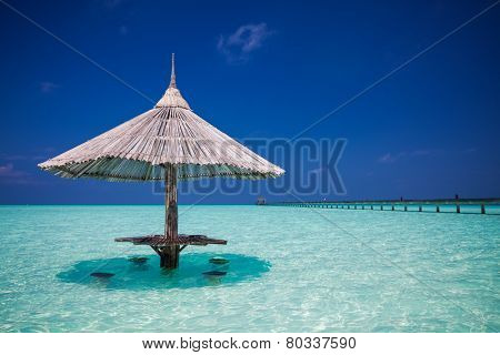Bamboo beach umbrella with bar seats in the water at Maldives