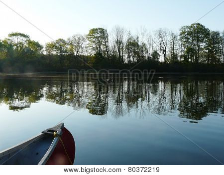 Red canoe and peaceful lake in the morning calm
