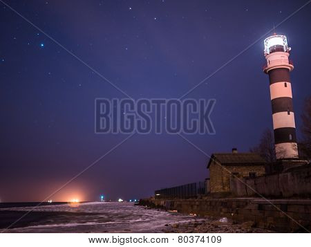Black And White Lighthouse At Night In Baltic Sea Beach