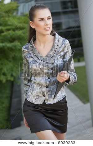 Young Woman Walking With Folder