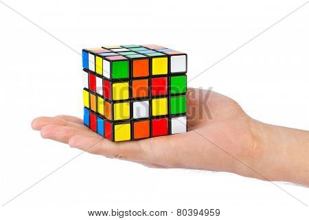 MOSCOW, RUSSIA - August 31, 2014: Hands and Rubik's cube puzzle isolated on the white background. Cube was invented by a Hungarian architect Erno Rubik in 1974.