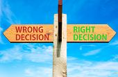 Wooden signpost with two opposite arrows over clear blue sky Right Decision and Wrong Decision Right choice conceptual image poster