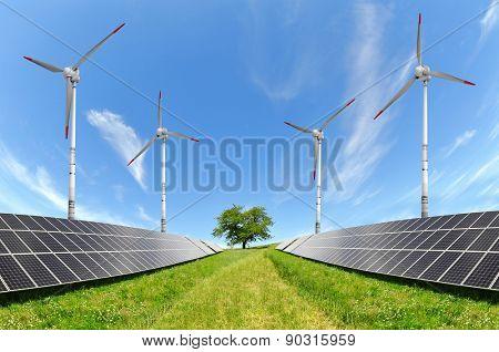Solar energy panels and wind turbines on meadow. Alternative energy.