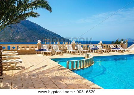 Swimming pool and sunbeds under palm tree, Greece