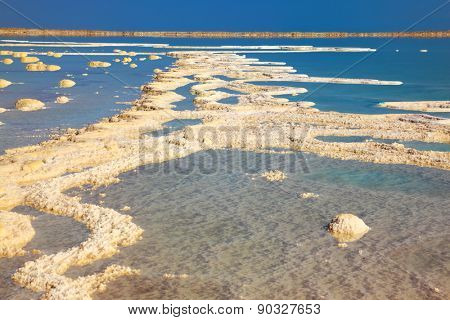 The picturesque road from the evaporated salt in the Dead Sea. Salt formed long paths with scalloped edges. Israel in October