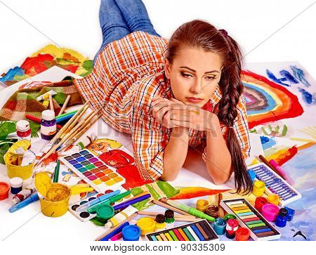 Unhappy artist woman lying on paint palette. Creative crisis.
