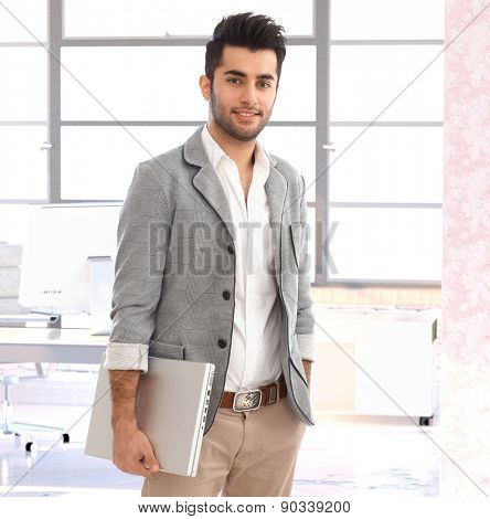 Portrait of modern young handsome arabian businessman at office, smiling.