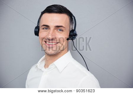 Smiling young male operator in headphones looking at camera over gray background