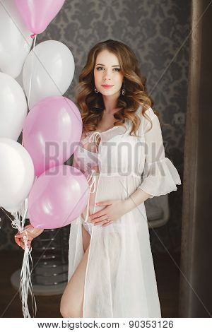 Pregnant beautiful woman with bunch of balloons.