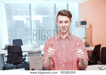 Portrait of office worker shoving thumbs-up