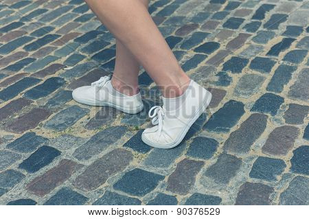 Legs Of Woman Standing On Cobbled Street