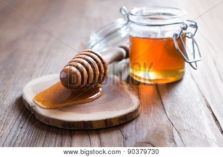 Honey in jur with wooden dipper in rustic style