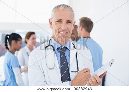 Confident male doctor smiling at camera in medical office