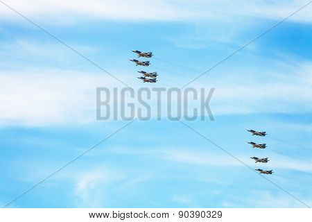 flight of military battleplane aircrafts in white clouds in blue sky poster