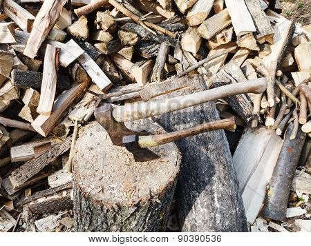 pile of wood deck for chopping firewood two axes on village yard poster