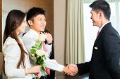 Asian Chinese Hotel Manager or director or supervisor welcome arriving VIP guests with roses on arrival in luxury or grand hotel poster