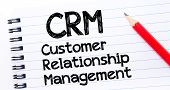 CRM acronym as Customer Relationship Management Text written on notebook page red pencil on the right. Concept image poster