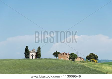 Cappella della Madonna di Vitaleta church with cypress trees and a farm in a field in the Orcia Valley in Tuscany Italy. poster