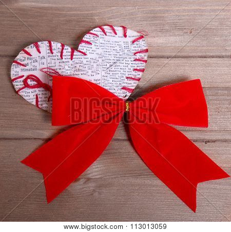 The Self-made Heart Sewed From A Slice Of The Newspaper And A Red Velvet Bow On A Wooden Table