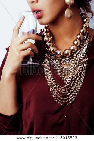 young african-american woman drinking champagne, holding glass, wearing lot of golden jewelry