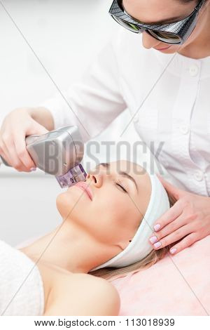 Experienced young therapist is curing female skin