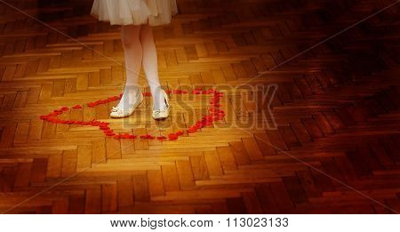 little bridesmaid girl legs in white dress on wedding dancefloor with rose petals.