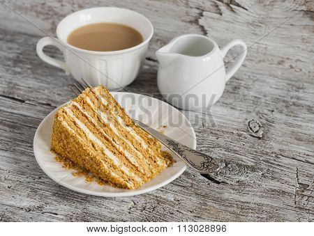 Piece Of Honey Cake And Tea With Milk On The Light Rustic Wooden Table