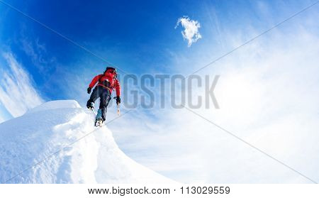 Mountaineer arrive at the summit of a snowy peak. Concepts: determination, courage, effort, self-realization. Sunny winter day, european Alps.
