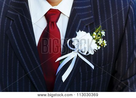 close-up black jacket groom on their wedding day with a red tie and lapel buttonhole.