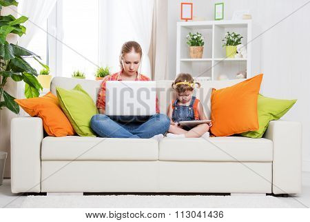 Mother And Child With Computer And Tablet At Home, According To The Concept Of Internet
